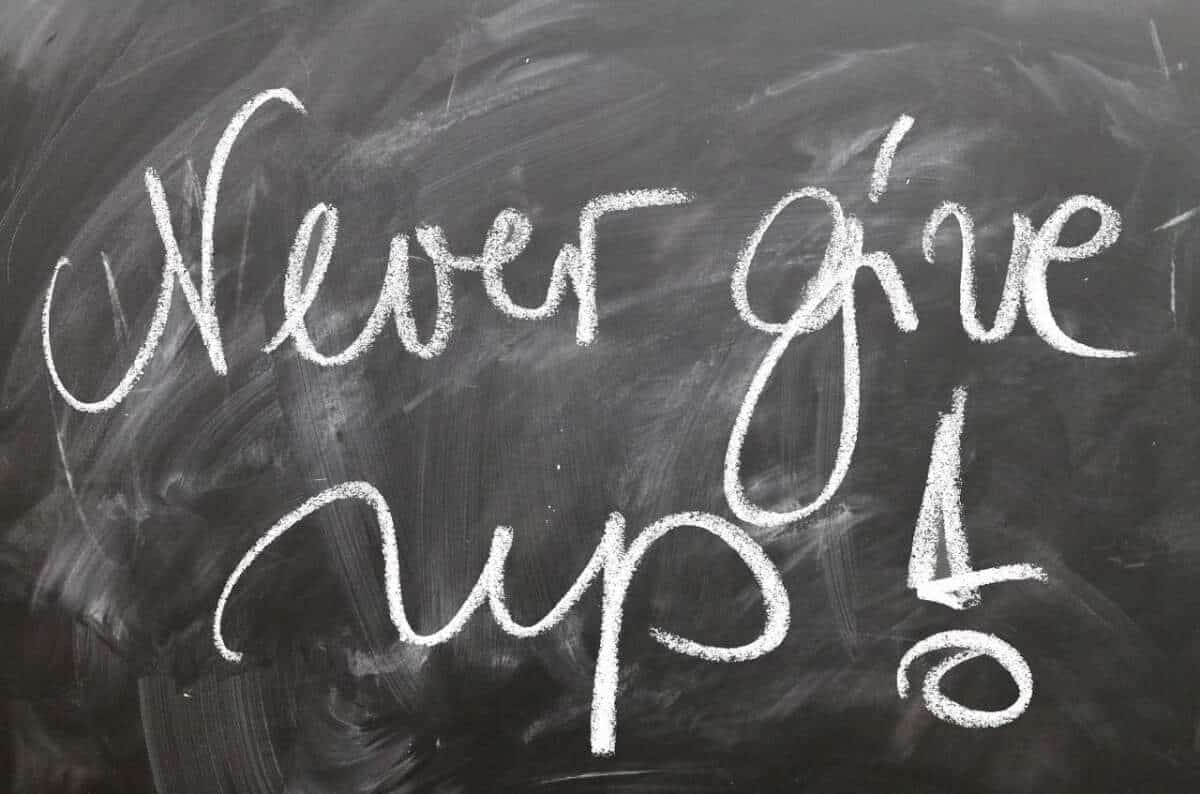 Black board with never give up written on it.