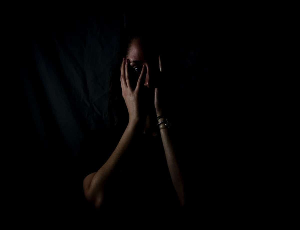 woman in dark covering her face
